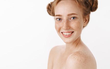 Tiro de cintura para arriba de mujer pelirroja femenina linda y tierna con peinado de bollos divertidos y pecas en el cuerpo sonriendo ampliamente posando sobre fondo gris con loción para hidratar la piel