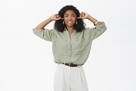 Hate living near club. Irritated displeased and pissed young attractive dark-skinned businesswoman feeling disturbed by loud annoying sound closing ears with index fingers clenching teeth from dislike Stock Photo