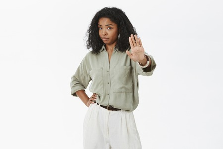 Hold, stay there. Portrait of bossy confident and displeased adult dark-skinned female with curly haircut holding hand on waist pulling palm towards camera in stop gesture prohibiting come closer