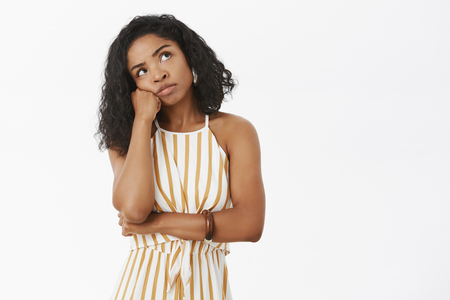 Thoughtful sad and bored african american female in striped yellow overalls leaning head on fist looking at upper right corner thinking talking to herself in mind looking concerned and tired
