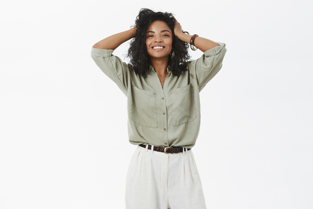 Pretty energized and feminine happy african american female satisfied with new hairstyle after visiting hairdresser making her more confident and joyful, touching hair and smiling at camera
