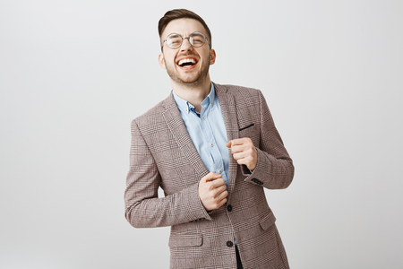 Guy feeling taste of success and wealth. Portrait of joyful optimistic handsome male with bristle in glasses and stylish jacket laughing out loud with raised feeling happy after signing promising deal
