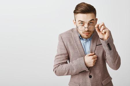 Studio shot di divertente impiegato maschio nerd in giacca alla moda con acconciatura alla moda che guarda da sotto gli occhiali toccando il bordo degli occhiali essendo incuriosito e interessato mentre ascolta il segreto di un amico