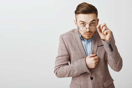 Studio shot of funny nerdy male office worker in trendy jacket with trendy hairstyle looking from under glasses touching rim of eyewear being intrigued and interested while hearing secret of friend Stock Photo