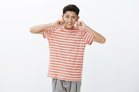 Cute chinese guy not used to crowded city life closing ears with index finger not hear loud noise of traffic jams clenching teeth displeased, being distracted with loud awful noise