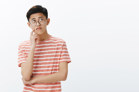 Smart asian guy solving puzzle in mind looking thoughtful and relaxed at upper right corner, thinking, making assumptions touching cheek while making up plan or decision, posing in glasses 免版税图像