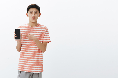 Pleased happy young cute asian guy in striped t-shirt standing to left side of copy space holding smartphone pointing at cellphone screen as showing awesome new phone to friends delighted Фото со стока