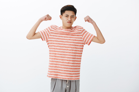 Look how strong I am. Portrait of self-assured funny young slim asian guy raising hands to show biceps or muscles, starting working out, straining and holding breath to look masculine