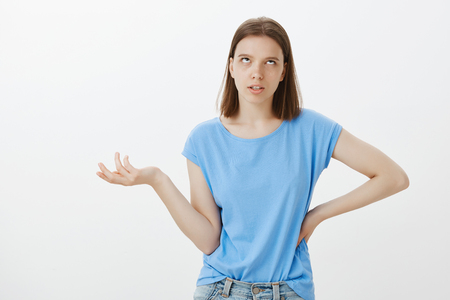 Indifferent careless snobbish woman in blue t-shirt, holding hand on hip, rolling eyelids and raising palm in unaware and uninterested gesture, having no interest Banque d'images