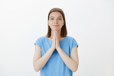 Girl found answers in buddhism, namaste. Portrait of relieved and relaxed attractive woman, smiling broadly while holding hands in pray, bowing or meditating, practicing yoga over grey wall Stock Photo