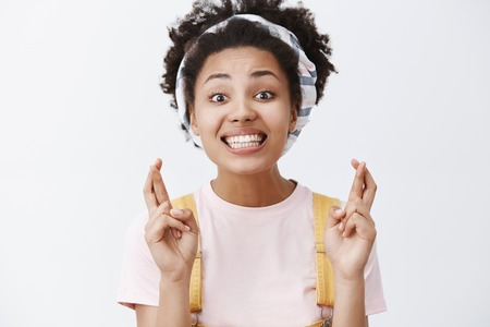 Keeping my fingers crossed for you. Portrait of good-looking cheering pretty African American woman in headband and overalls, smiling broadly while making wish, begging for good luck over grey wall
