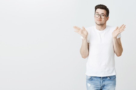 Sorry, my bad. Portrait of silly handsome young male model shrugging with raised palms near shoulders and light smirk, appologizing making mistake or being unaware what happening over white background 스톡 콘텐츠