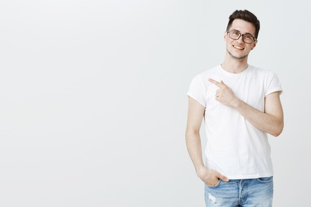 Portrait of charismatic relaxed and friendly young caucasian man in glasses and t-shirt pointing left at copy space, smiling assuring and suggesting customer chose product over gray background 写真素材