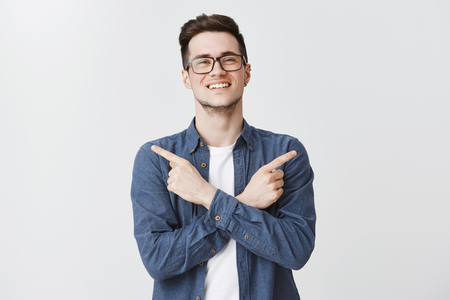 Pleasant friendly-looking charming smiling guy in glasses and blue shirt crossing hands on body, pointing sideways with satisfied grin giving two choices posing delighted over gray background