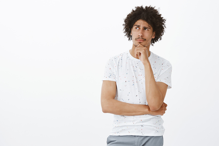 Handsome guy thinking if he did right thing. Thoughtful relaxed and handsome mature man with moustache and afro haircut, holding hand in chin and gazing left while thinking, making decision