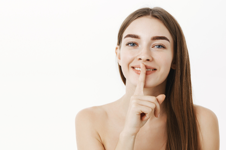 Close-up shot of feminine tender and happy charming brunette female posing naked over gray background telling beaty secret and making shh sigh, showing shush gesture with index finger over mouth