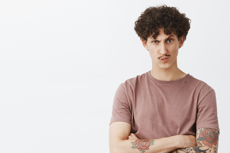 Bossy displeased and suspicious good-looking stylish jewish guy with curly hair and moustache in brown t-shirt holding hands crossed on chest smirking and frowning doubtful over gray wall