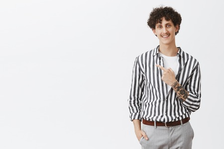 Studio shot of relaxed and chill friendly-looking nice urban male with moustache tattoos and curly hair pointing at upper left corner smiling with pleased and delighted look in striped cool shirt Stock Photo