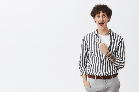 Guy being excited before making new tattoo yelling from delight and happiness standing amused and thrulled in striped cool shirt pointing at upper left corner posing over gray background