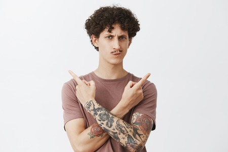 Unsure hesitating cute young guy with curly dark hair and fancy moustache smirking and frowning suspicious and doubtful pointing left and right in different sides cannot choose what pick