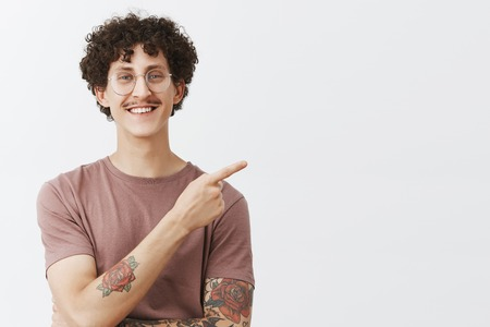 You would not find better place for advertising. Friendly handsome and creative young stylish male model with curly hairstyle tattoos and moustache smiling joyfully pointing at upper right corner Stock Photo