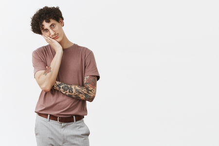 Guy hates sitting at home without action. Portrait of bored handsome and stylish urban young male with moustache, tattooed arm and curly hair leaning on palm indifferent and gloomy Stock Photo