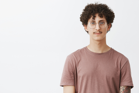 Waist-up shot of friendly-looking calm and carefree young man with moustache and curly hairstyle wearing glasses and brown t-shirt smiling cute standing casually over gray background Stock Photo