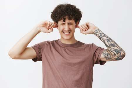 Waist-up shot of displeased intense modern hipster male student with moustache curly hair and tattooed arm clenching teeth from discomfort covering ears with index fingers not hear annoying loud sound Stock Photo