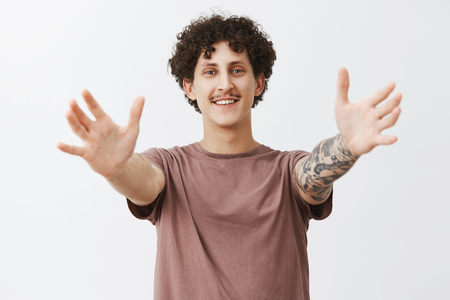 Come into my hands. Portrait of friendly pleased and joyful stylish urban male with cute moustache and curly dark hair pulling hands towards camera to give hug and smiling broadly over gray wall Stock Photo