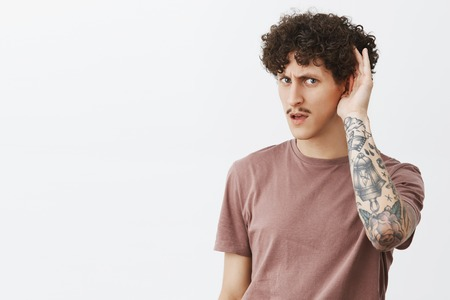 Say again cannot hear clearly. Portrait of intense stylish handsome young male with curly hairstyle moustache and tattooed arm holding hand near ear asking to repeat question gazign focused at camera Stock Photo