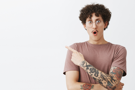 Waist-up shot of excited and impressed emotive attractive male student with stylish moustache curly dark hair and tattooed arm gasping folding lips from amazement and pointing at upper left corner