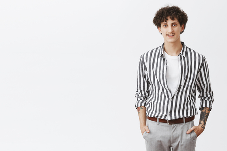 Waist-up shot of stylish modern young hipster guy in striped shirt and gray pants holding hands in pockets with moustache dark curly hair and tattoos dressing up for date over gray background