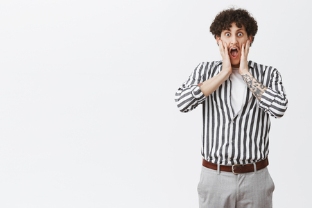 Guy yelling seeing friend naked. Portrait of shcoked and stunned good-looking stylish male with moustache and curly hair in striped shirt screaming with hands near opened mouth posing over gray wall