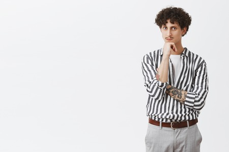 Smart and thoughtful young creative male entrepreneur with tattooed arm moustache and curly hair in trendy formal striped shirt and pants leaning on fist and looking seriously at camera
