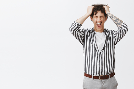 Studio shot of depressed young guy with moustache in striped shirt losing temper screaming out loud pulling hair out of head being fed up and pissed off by stupid boss posing over gray background
