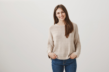 Friendly newbie meets with new teammates. Indoor shot of shy attractive female in casual pullover standing with hands in pockets and tilting head while smiling at camera, talking to stranger Stock Photo