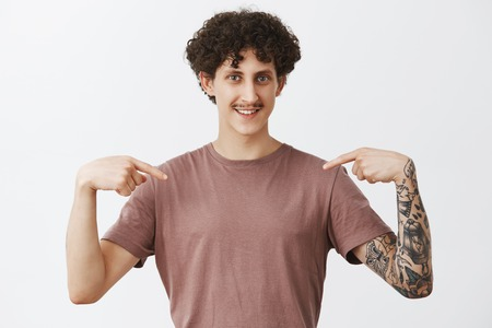 Skillful and smart guy pointing at himself while recommending give job position him. Proud, confident friendly stylish male model with moustache and curly hairstyle indicating at chest and smiling Stock Photo