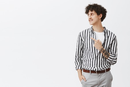 Portrait of stylish good-looking and confident modern hipster male model with moustache curly dark hair and tattoos pointing and gazing left with pleased charming smile over gray background Stock Photo