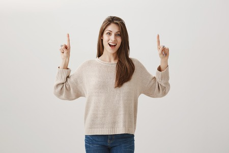 Soon we will be in plane, travelling to warm countries. Portrait of excited beautiful caucasian brunette pointing up while being thrilled with good news, showing direction over gray background