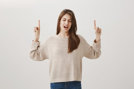 Shoot, it is raining again. Portrait of gloomy upset attractive slender woman pointing up with raised hands, crying or whining with closed eyes, being displeased with bad weather over gray background Stock Photo