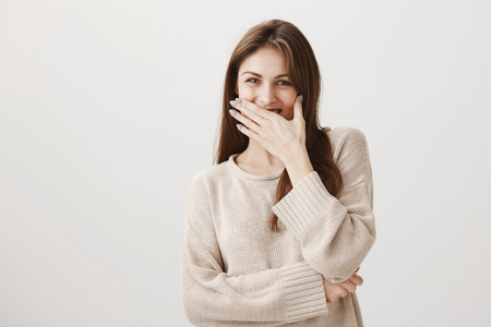 Girl likes funny jokes. Positive attractive european female chuckling and covering mouth with palm, fooling around with coworkers and laughing while discussing life issues, standing over gray wall