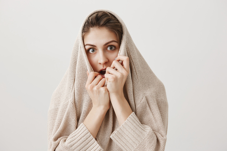 Girl watches horror film alone, trembling from fear. Portrait of adorable european female pulling sweater on head and looking through collar with shocked and scared expression, gasping over gray wall Stock Photo