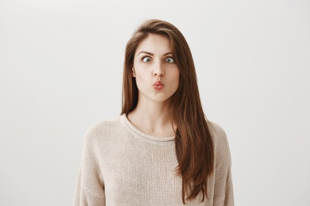 Woman goes crazy from boredom. Portrait of funny childish european girl making faces, squinting and puckering lips, trying to look at her nose, standing against gray background Stock Photo