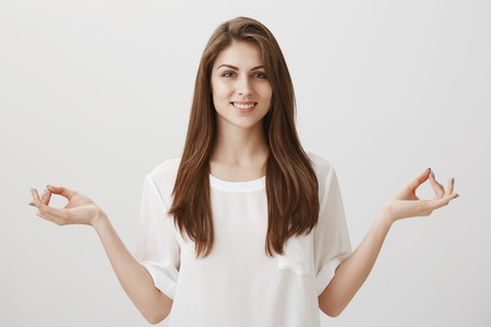 Calm young soul with meditation. Studio shot of relaxed friendly modern female standing with spread hands and zen gesture, doing yoga, smiling broadly, feeling relieved and renewed