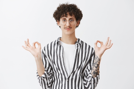 Keep calm and release peace. Friendly-looking relaxed and chill smiling cute guy with moustache and curly hairstyle raising hands with okay or zen gesture meditating, practicing yoga over gray wall