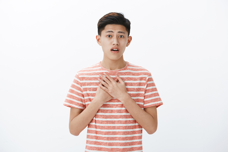 Touched and delighted sensitive young asian teenage boy raising eyebrows, open mouth from surprise as pressing hands to chest being grateful and amazed with touching surprise over gray background