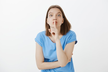 Shh, you cannot tell anyone, promise. Excited good-looking female office worker in blue t-shirt, bending towards camera, making shush gesture with index finger over mouth, telling rumor or secret Stock Photo