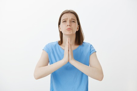 Please help me out friend. Portrait of gloomy good-looking woman in blue t-shirt, bending towards camera with hands in pray, making upset face, begging for forgiveness, asking favour or apology Stock Photo