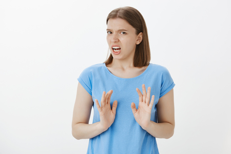 Portrait of displeased and disgusted european woman in blue t-shirt, shaking palms in rejection gesture, disliking idea and declining it, expressing antipathy and disappointment over grey wall Stock Photo