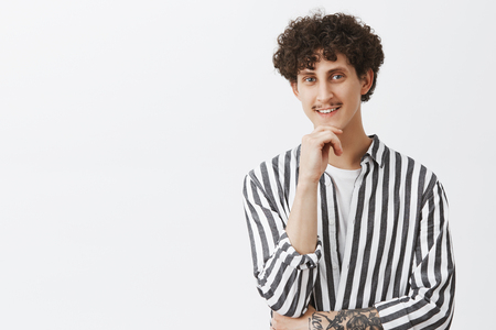 Creative and stylish hipster guy with moustache and curly dark hair in trendy striped shirt holding hand on chin and smiling from interest and curiosity being intrigued by shop assistant